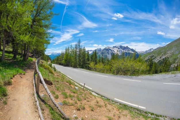 Paved two lane road in scenic alpine landscape and moody sky, fisheye view. summer adventure and roadtrip at col d'izoard, france.