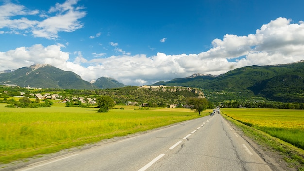 Paved two lane road in scenic alpine landscape and moody sky. panoramic view from car mounted camera.