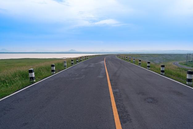 Pavement asphalt road view leads to the horizon at pasak chonlasit dam beautiful scenery of road