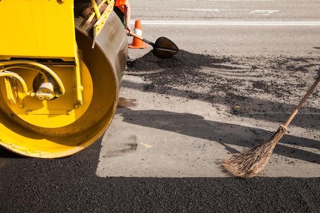 고속도로 건설 중 자갈 바닥 위에 신선한 아스팔트 또는 역청을 깔는 포장 기계