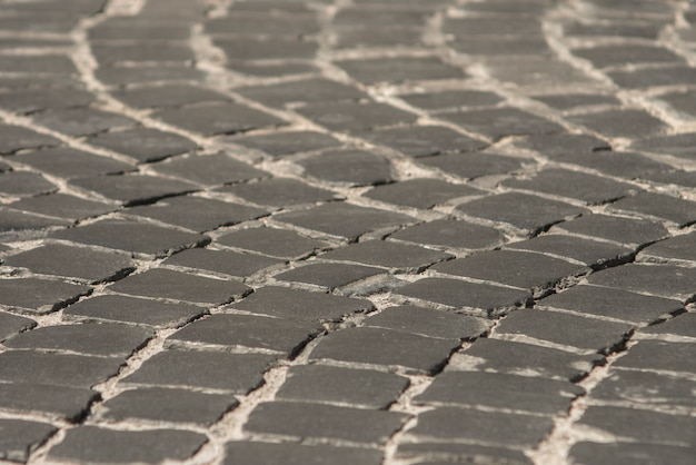 Pavement in the old town of black cobblestone. background texture