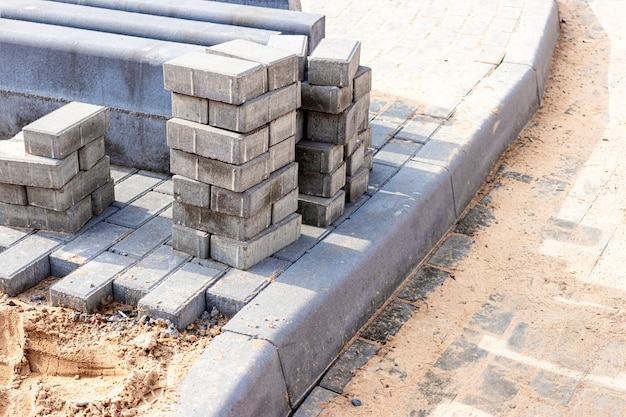 포장 도로 수리 및 보도에 포장용 석판을 깔고 배경에 쌓인 타일 큐브. 도시의 보행자 구역에 포장 석판을 깔고 모래를 채우십시오. 도로 타일 및 연석.