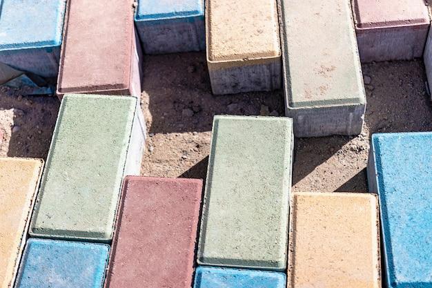 포장 도로 수리 및 보도에 포장용 석판을 깔고 배경에 쌓인 타일 큐브. 도시의 보행자 구역에 포장 석판을 깔고 모래를 채우십시오.