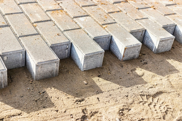 Pavement repair and laying of paving slabs on the walkway, stacked tile cubes on the background. laying paving slabs in the pedestrian zone of the city, sand filling. road tiles and curbs.