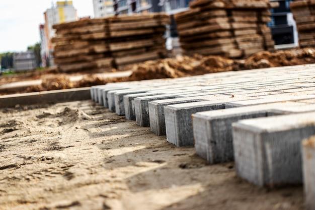 Ремонт тротуара и укладка тротуарной плитки на подготовленную поверхность на фоне кубиков плитки. укладка тротуарной плитки в пешеходной зоне города. тротуарная плитка и бордюры.