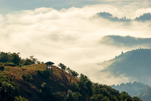 Pavilion is located in middle of the mountain and there is fog with morning light.