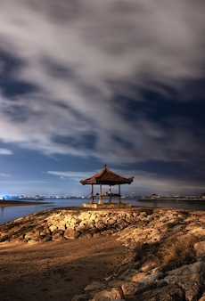 Павильон на каменной пристани с облачностью на пляже санур на бали