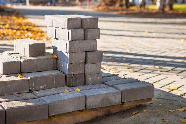 포장 벽돌은 도시 광장의 포장용 석판을 깔기 위해 팔레트에서 건설 작업을 할 준비가되었습니다. 공원 가을의 거리에서 나뭇잎. 프리미엄 사진