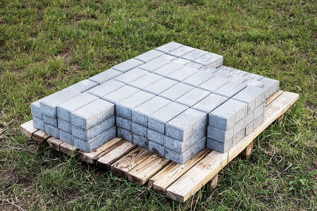 녹색 잔디에 설치를 위해 준비된 팔레트에 슬래브를 포장합니다. 콘크리트 포장 슬래브로 도로 포장.