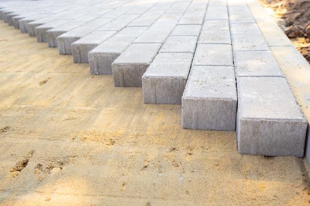 보도 건설의 모래 과정에 포장 슬래브 또는 포장 돌이 깔려 있습니다.