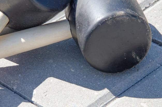 敷石舗装背景。フォアグラウンドにツールラバーハンマーを取り付ける