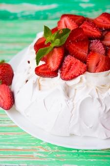 소박한 배경에 딸기와 크림을 넣은 파블로프의 케이크, 선별적인 초점, 클로즈업