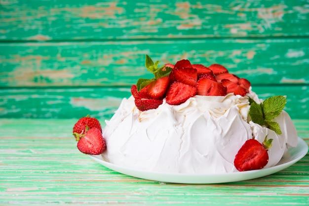 소박한 배경에 딸기와 크림을 넣은 파블로프의 케이크, 선별적인 초점, 복사 공간