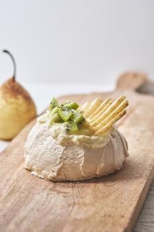 치즈 크림, 레몬 쿠르드, 키위, 배가 들어간 파블로바 케이크.
