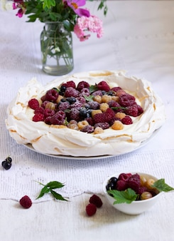 Pavlova cake with cream and berries and a bouquet of flowers on a light background. rustic style, selective focus.