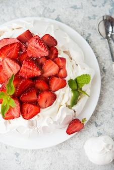 밝은 배경에 머랭과 신선한 딸기를 곁들인 파블로바 케이크, 선별적인 초점, 위쪽 전망