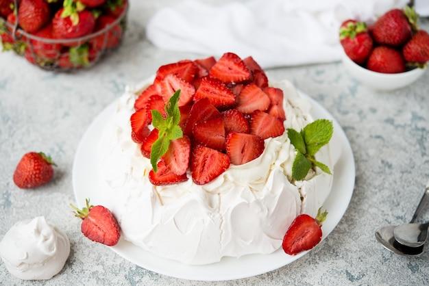 밝은 배경에 머랭과 신선한 딸기를 넣은 파블로바 케이크, 선별적인 집중