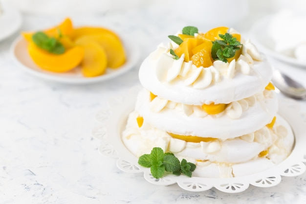 Pavlova cake with peach on a white plate