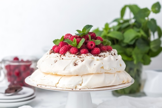 Pavlova cake with raspberries on a white cake stand