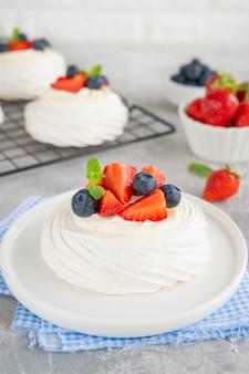 접시 위에 휘핑크림과 신선한 딸기를 얹은 파블로바 머랭 케이크