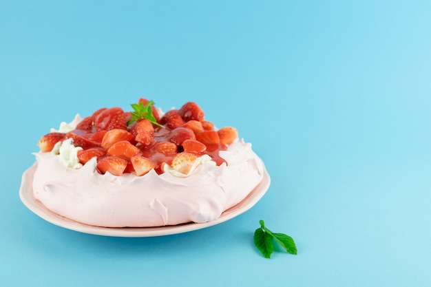 Pavlova red fruit cake on a blue table. pastry concept.