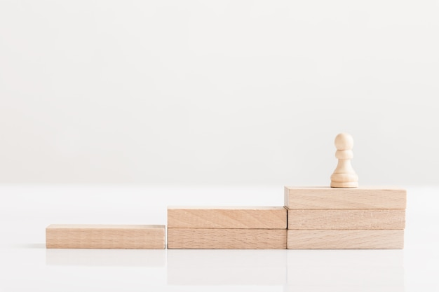 Pawn chess piece on a staircase of wooden bricks , conceptual of business vision.