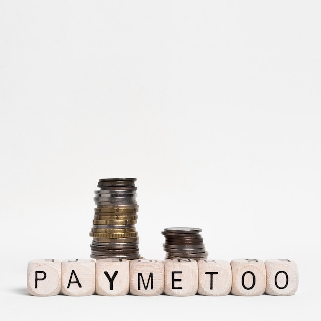 Pay me too written on wooden cubes with coins