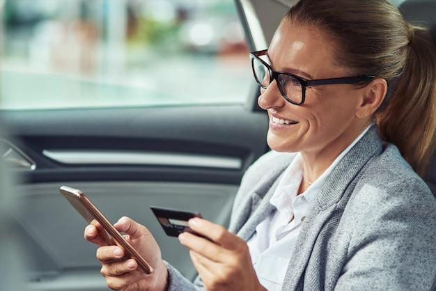온라인으로 지불하십시오. 자동차, 온라인 결제 및 쇼핑 개념의 뒷좌석에 앉아있는 동안 그녀의 스마트 폰과 신용 카드를 사용하여 뭔가를 구입하는 행복 중간 세 사업 여자