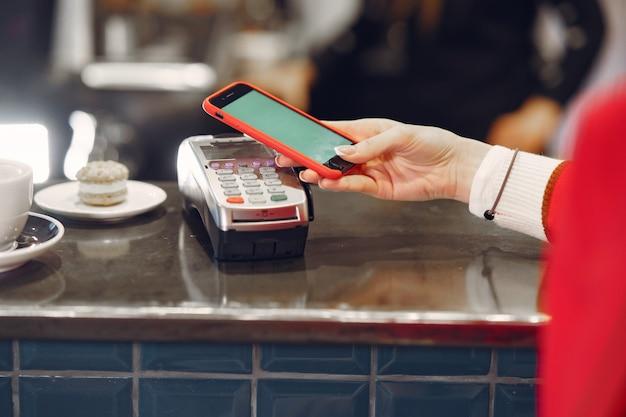 非接触型pay passテクノロジーを使用してスマートフォンでラテの支払いをしている女の子