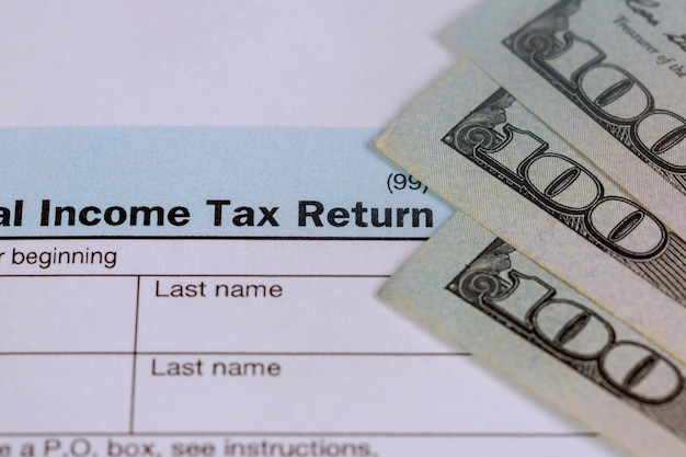 Pay tax concept usa tax form 1040 with 100 us dollar bills.
