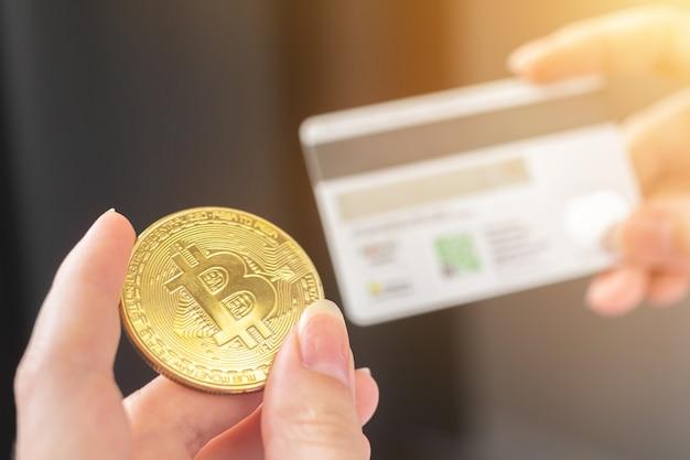 Оплата биткойнами, оплата золотой монетой криптовалюты и кредитной картой. женщина переводит деньги с новой фотографией концепции виртуальных денег
