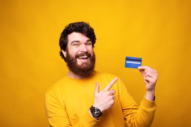 カードで支払う。 1つを保持しているひげを生やした男はそれを指して、カメラに微笑んでいます。