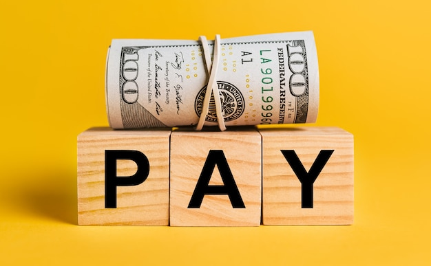 Pay with money on a yellow surface. the concept of business, finance