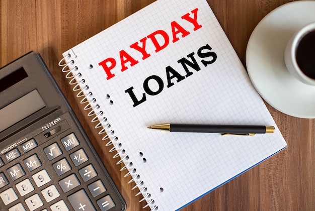 Payday loans written in a white notepad near a calculator and a cup of coffee on a dark wooden background