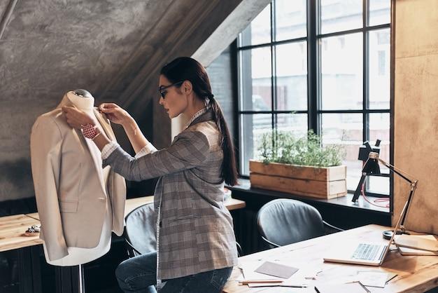 Уделять внимание каждой детали. серьезная молодая женщина в очках регулирует воротник куртки на манекене, стоя в своей мастерской