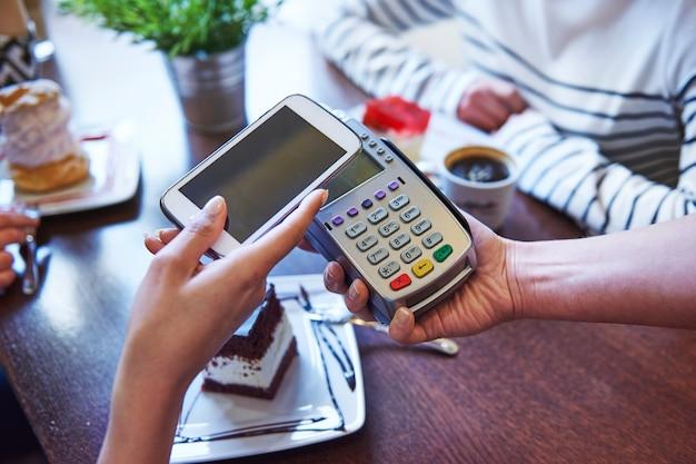 携帯電話でコーヒーを支払う