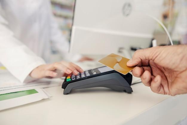薬局でのカードによる支払い。男性の手は端末に支払いクレジットカードまたはデビットカードを提供し、薬剤師の女性の手はpinコードを入力します。治療薬の購入