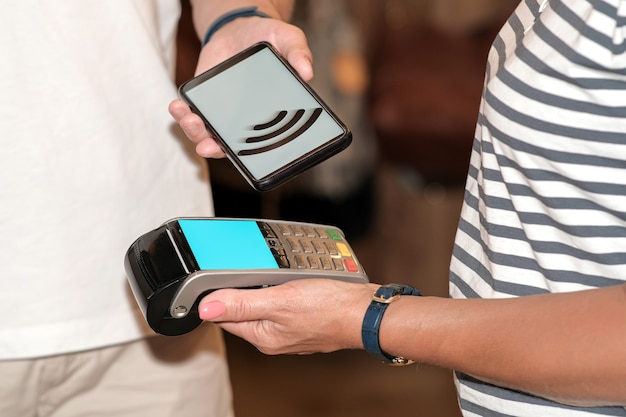 Payment by card, in the payment terminal. electronic money. mobile banking. shopping complex.