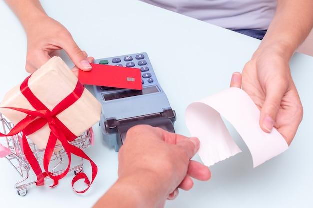 신용 카드로 지불, 현금 등록기에서 선물 구매를 위한 은행 카드, 계산원의 수표를 주는 손. 비즈니스 개념입니다. 블랙 프라이데이 컨셉