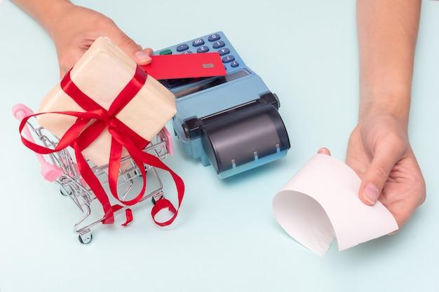 신용 카드로 지불, 현금 등록기에서 선물 구매를 위한 은행 카드, 계산원의 수표를 주는 손. 비즈니스 개념입니다. 휴가 선물을 구입. 블랙 프라이데이 컨셉