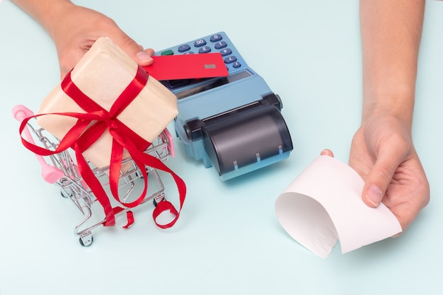 Payment by credit card, bank card at the cash register for the purchase of a gift, the hand giving the cashier's check. business concept. buying a gift for the holiday. black friday concept