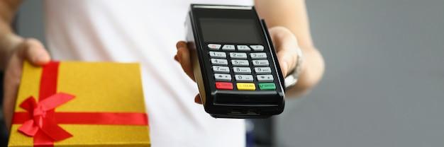 터미널에서 신용 플라스틱 은행 카드로 선물 상자가 있는 택배로 지불