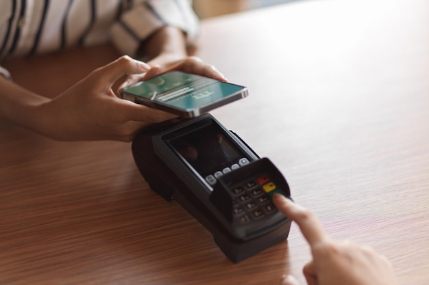 Payment by payment terminal on the wooden desk