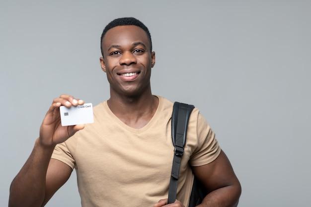 お支払カード。クレジットカードを示して立っている肩越しにバッグと幸せな笑顔の若いアフリカ系アメリカ人の男