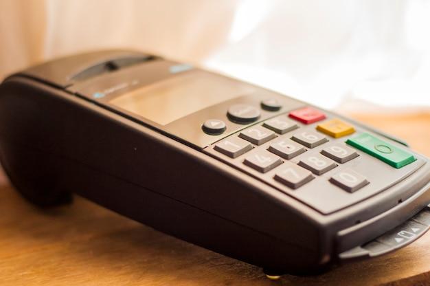 은행 터미널의 결제 카드. 전자 지불의 개념. 슈퍼마켓에서 터미널 카운터. 핀을 기다리는 카드가있는 무선 pos 터미널