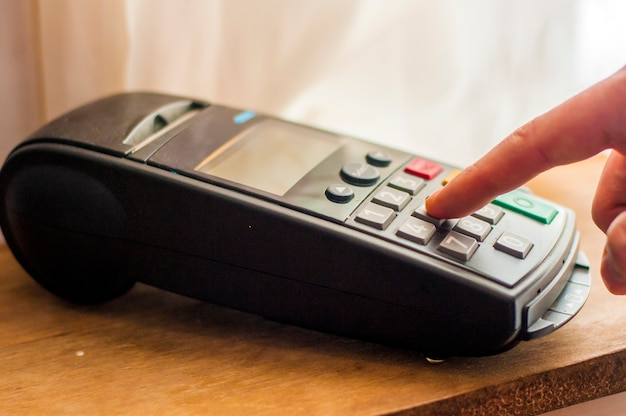 은행 터미널의 결제 카드. 전자 지불의 개념. 카드 기계의 핀 패드에 손 핀 코드 또는 pos 터미널 좋은 사진. 사업가 pos 터미널을 들고입니다.
