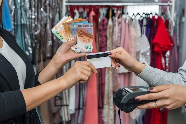 Payment in clothes store with terminal, credit card and cash