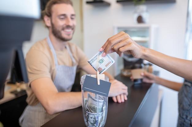 Оплата заказа. женская рука протягивает стодолларовую купюру для кофе и улыбающийся мужчина в фартуке за прилавком