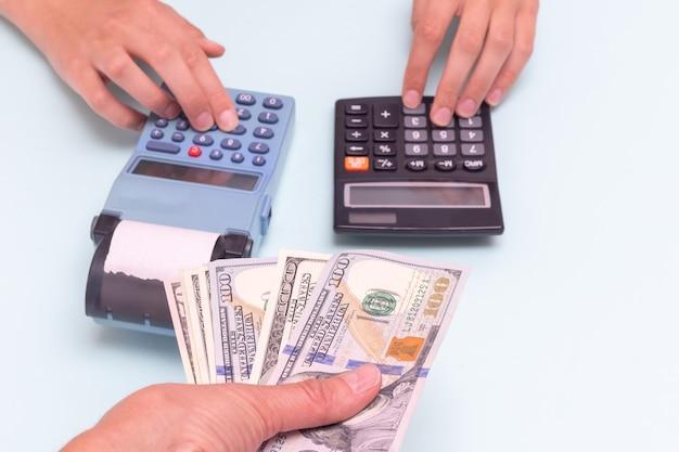 現金での購入の支払い。購入のために現金を与える手、レジのボタンを押す手、青い背景の電卓でコストを計算する手。ブラックフライデーのコンセプト