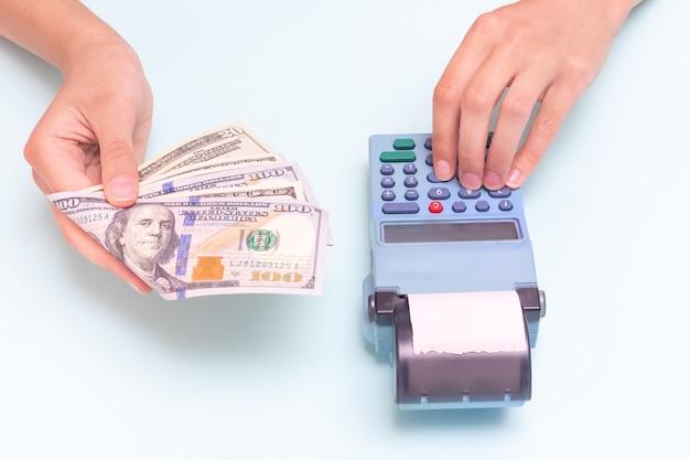 現金、ドルでの購入の支払い。青い背景に対してレジで数えて、現金を与える手のクローズアップと金額を入力する手。ビジネスコンセプト、小売、オンライン販売。